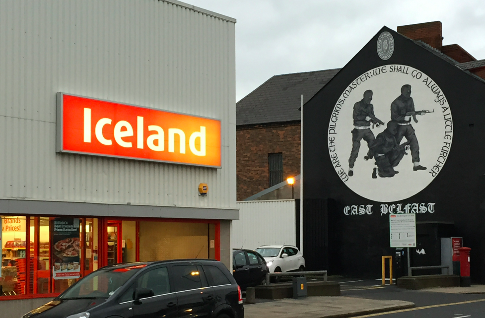 Armed men stare down at shoppers en route to Iceland.